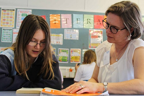 Shepparton High School teacher librarian educates and helps a school student with her literacy by reading together from a book